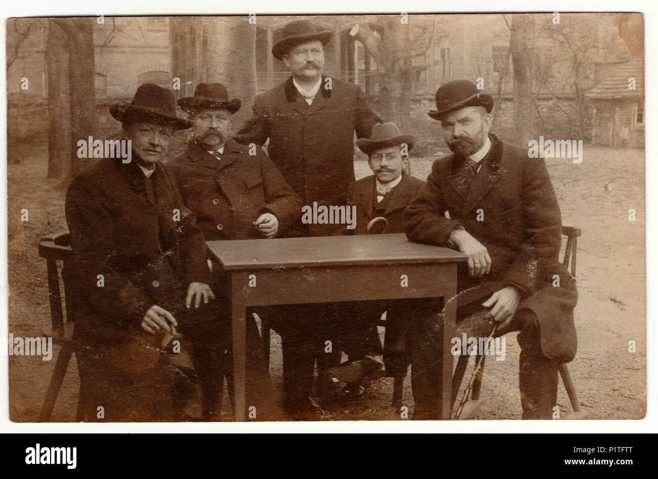 GERMANY - APRIL 14, 1907 Vintage photo shows men wear bowlers and sit at the table. Retro black & white photography. - Stock Image