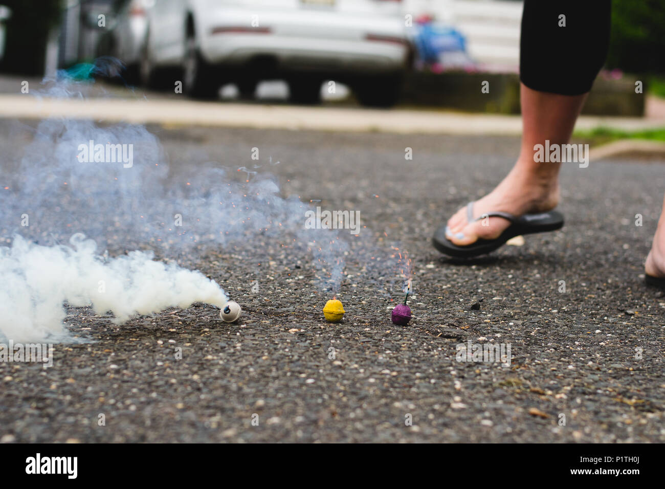 Three Smoke Bombs by Woman's Foot in Street - Stock Image
