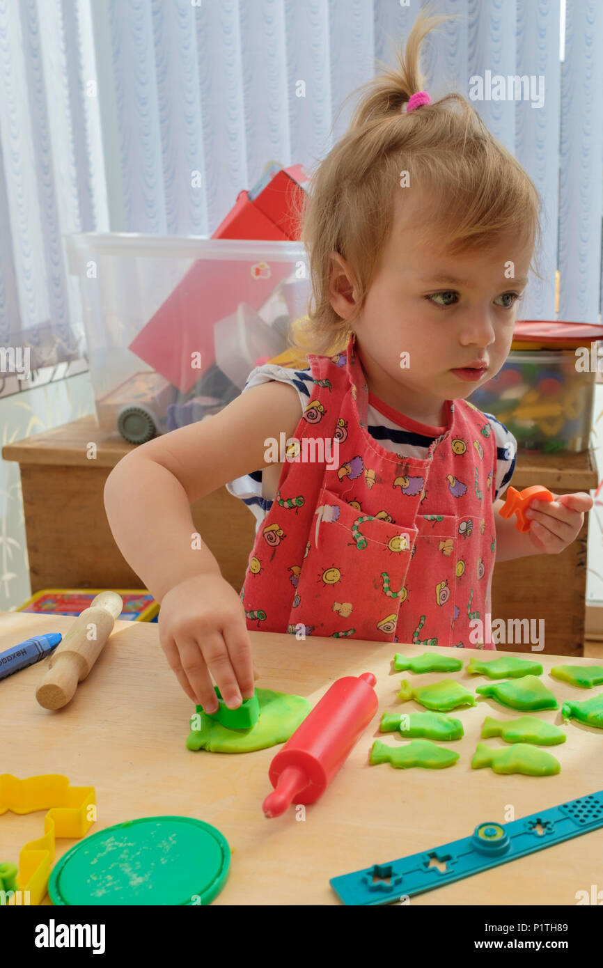 Happy young two year old girl playing and cutting out modelling dough clay. - Stock Image