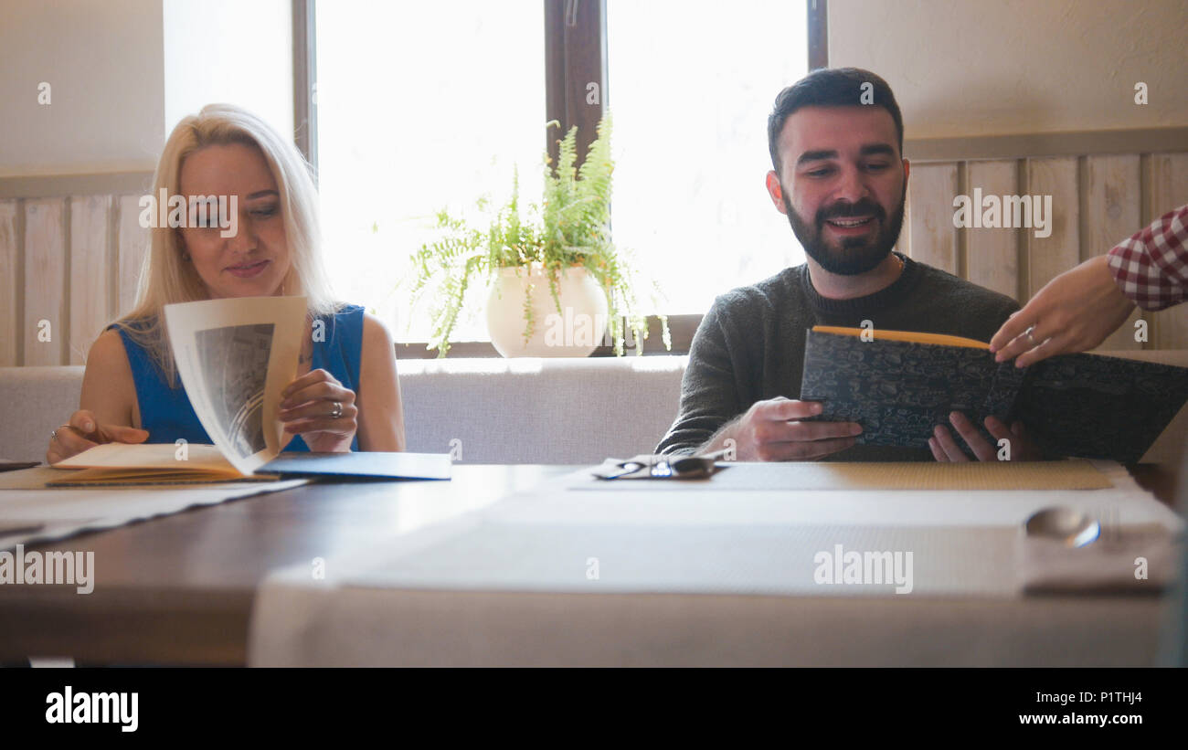 Happy caucasian couple takes the menu at the cafe - Stock Image