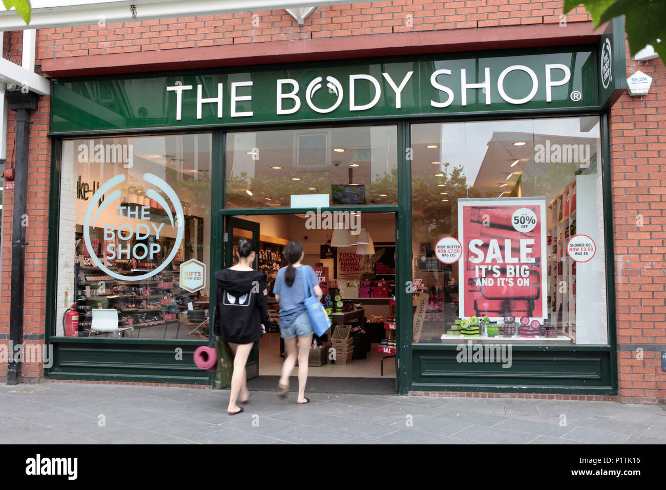 exterior view of THE BODY SHOP, with two young women entering. Shops and people shopping in Harrow, middlesex, London, UK - Stock Image