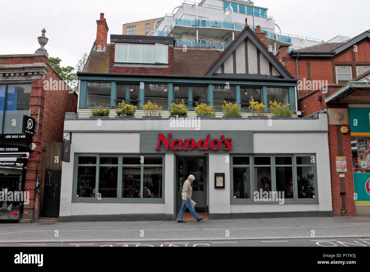exterior view of a NANDO'S restataurant. Shops and people shopping in Harrow, middlesex, London, UK - Stock Image