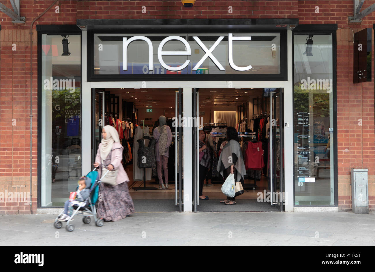 a next fashion outlet, exterior view. Shops and people shopping in Harrow, middlesex, London, UK - Stock Image