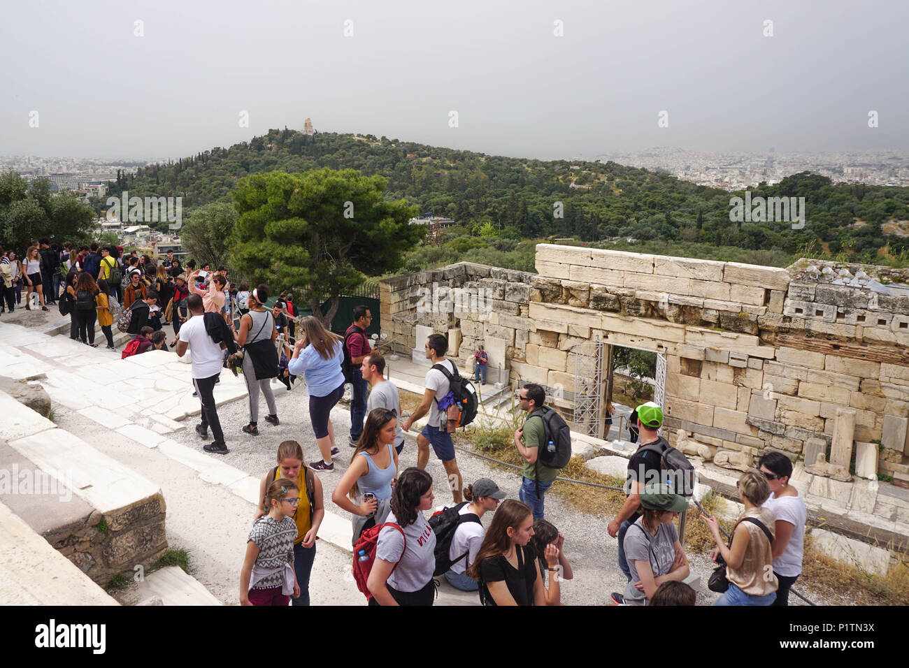 Athens, Greece - April 16, 2018: Tourists crowd the propyla (entrance) of the Acropolis of Athens, near the Roman-era Beulé Gate on the right. - Stock Image