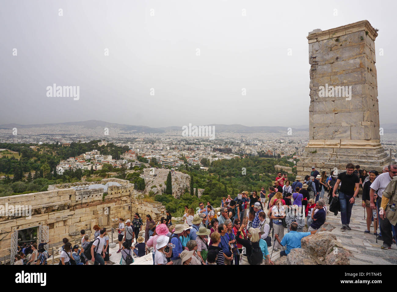 Athens, Greece - April 16, 2018: Tourists crowd the entrance of the Acropolis of Athens, under a hazy sky. The Roman-era Beulé Gate is on the right. - Stock Image