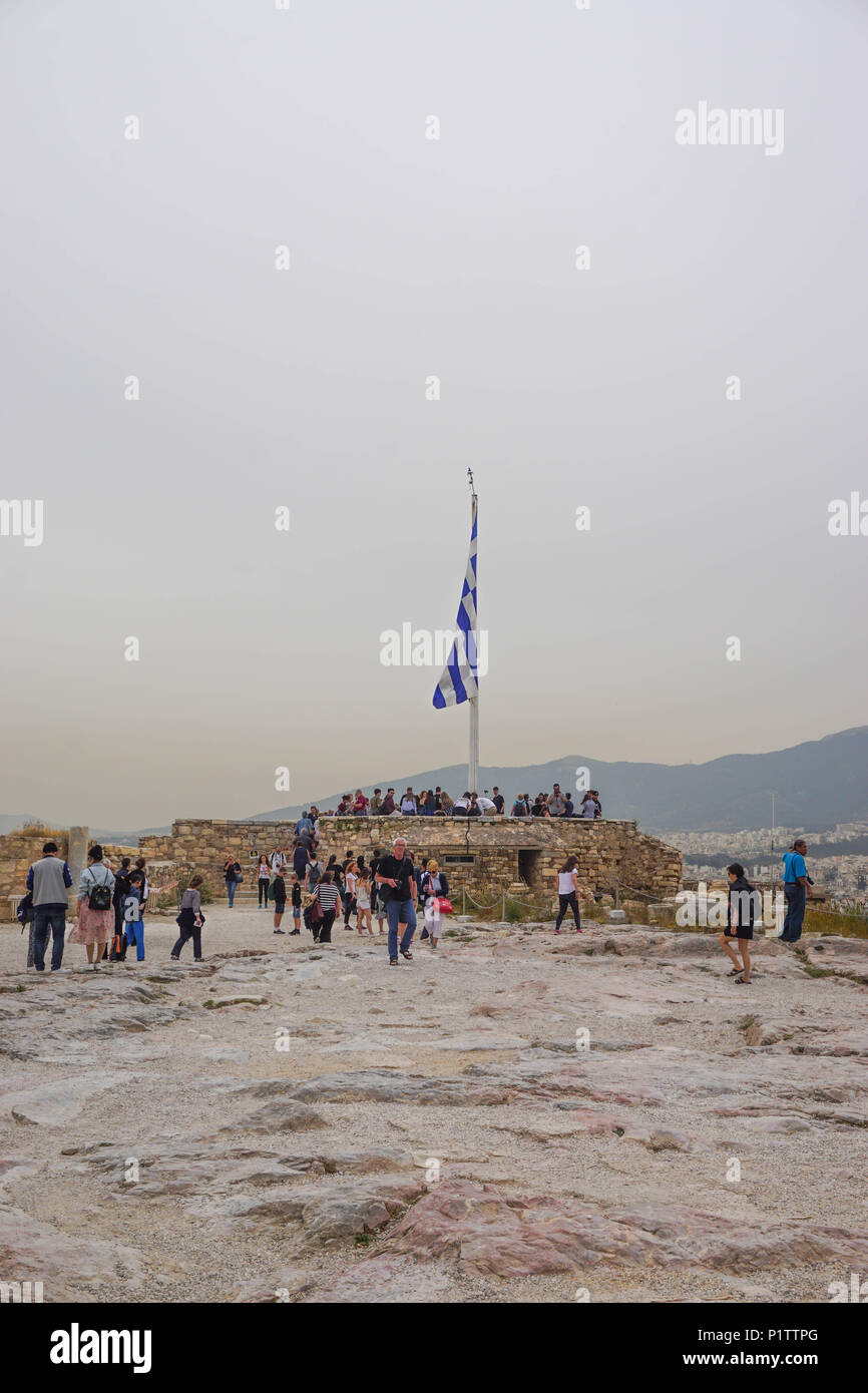Athens, Greece - April 16, 2018: Tourists gather around the Greek flag at the Acropolis of Athens, under a hazy sky caused by dust pollution. - Stock Image