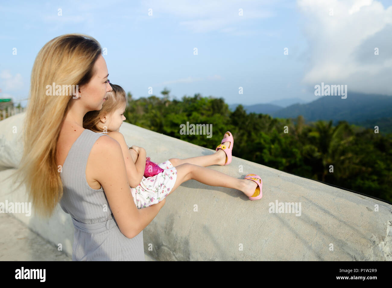 Young caucasian mother standing with little daughter in mountains background. - Stock Image