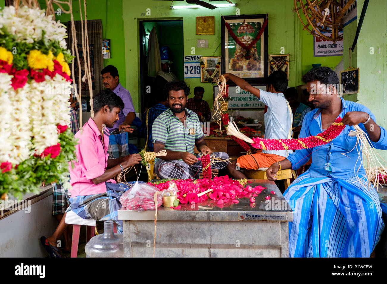 Indian men making flower garlands at Madurai Flower market, Mattuthavani, Madurai District, Tamil Nadu, India. - Stock Image