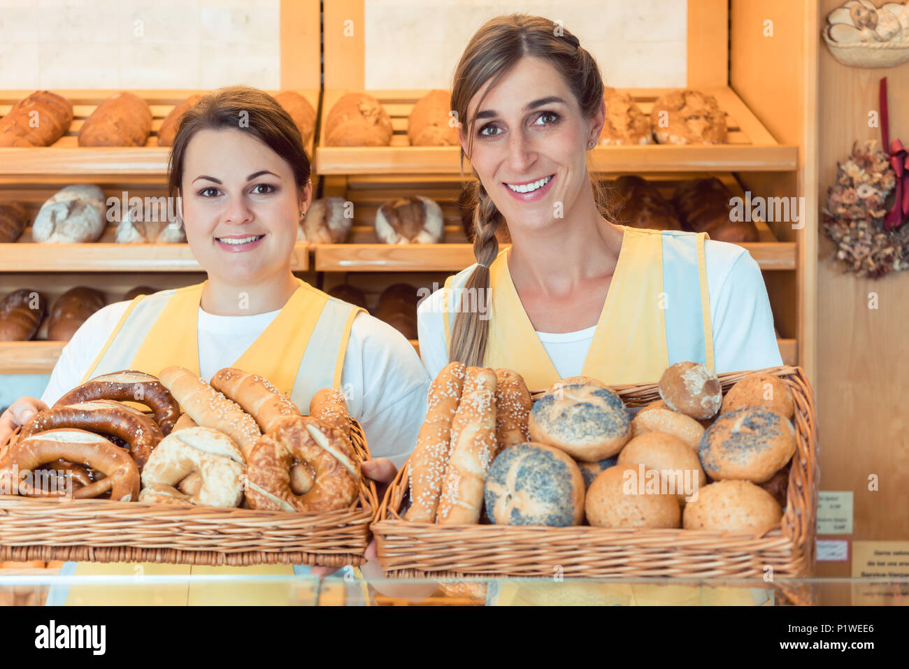 Two salesladies in bakery with basket of bread showing them to the camera - Stock Image