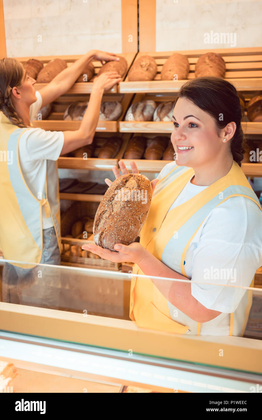 Two salesladies selling bread and other products in bakery shop working as a team - Stock Image