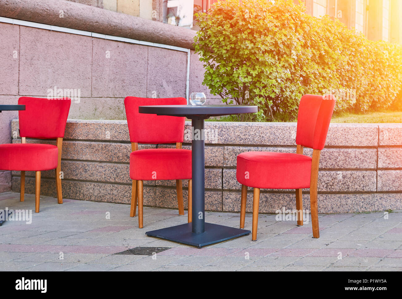 Comfortable chairs standing on pavement near small table in nice outdoor cafe on sunny day