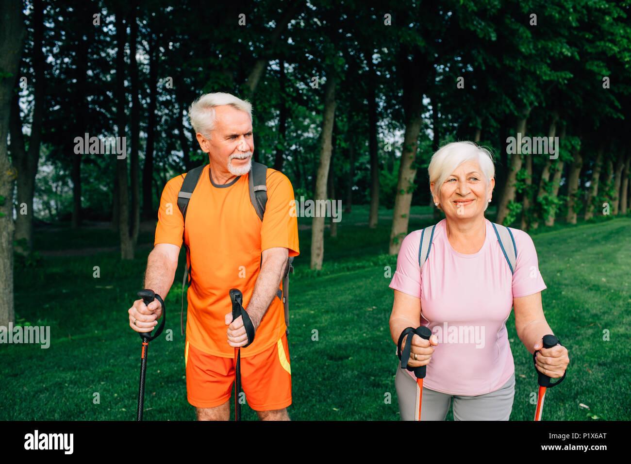 Senior couple hiking below trees, active lifestyles - Stock Image
