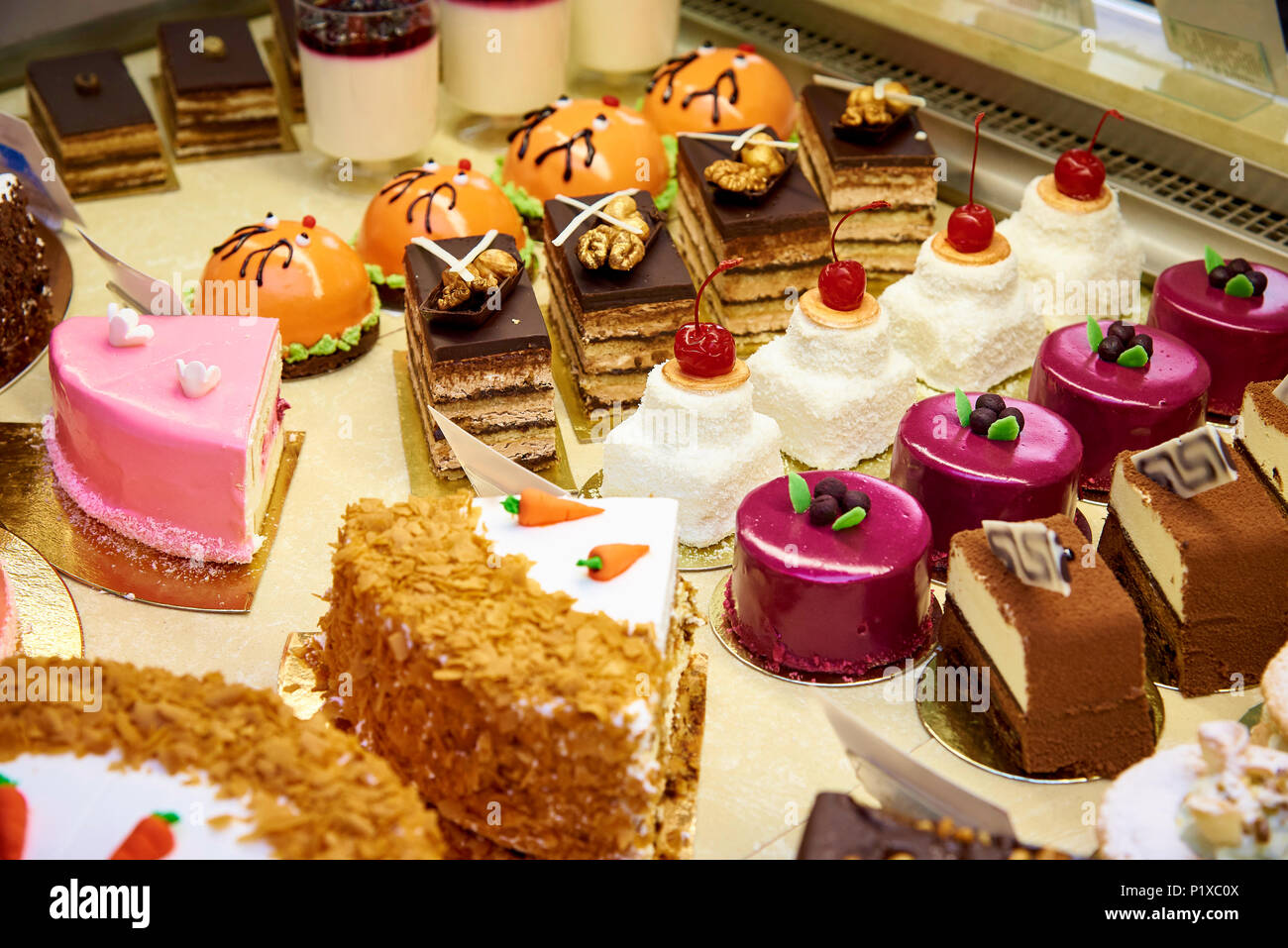 Rows of a variety of cooked desserts close-up in the display case. - Stock Image