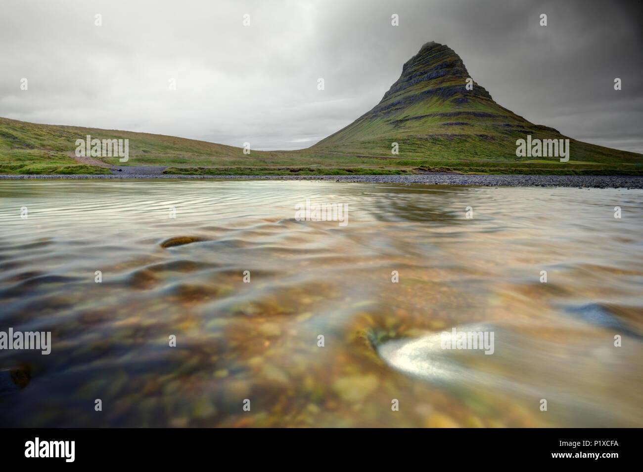 The Kirkjufellsa River flows below Kirkjufell (Church Mountain), Grundarfjordur, Snaefellsnes peninsula, West Iceland, Iceland - Stock Image