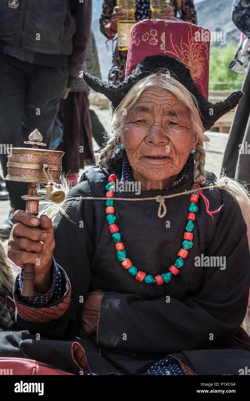 Lamayuru, India - June 19, 2017: Unidentified ladakhi old lady with the tibetan prayer wheel during buddhist festival in Lamayuru Gompa monastery, Lad - Stock Image