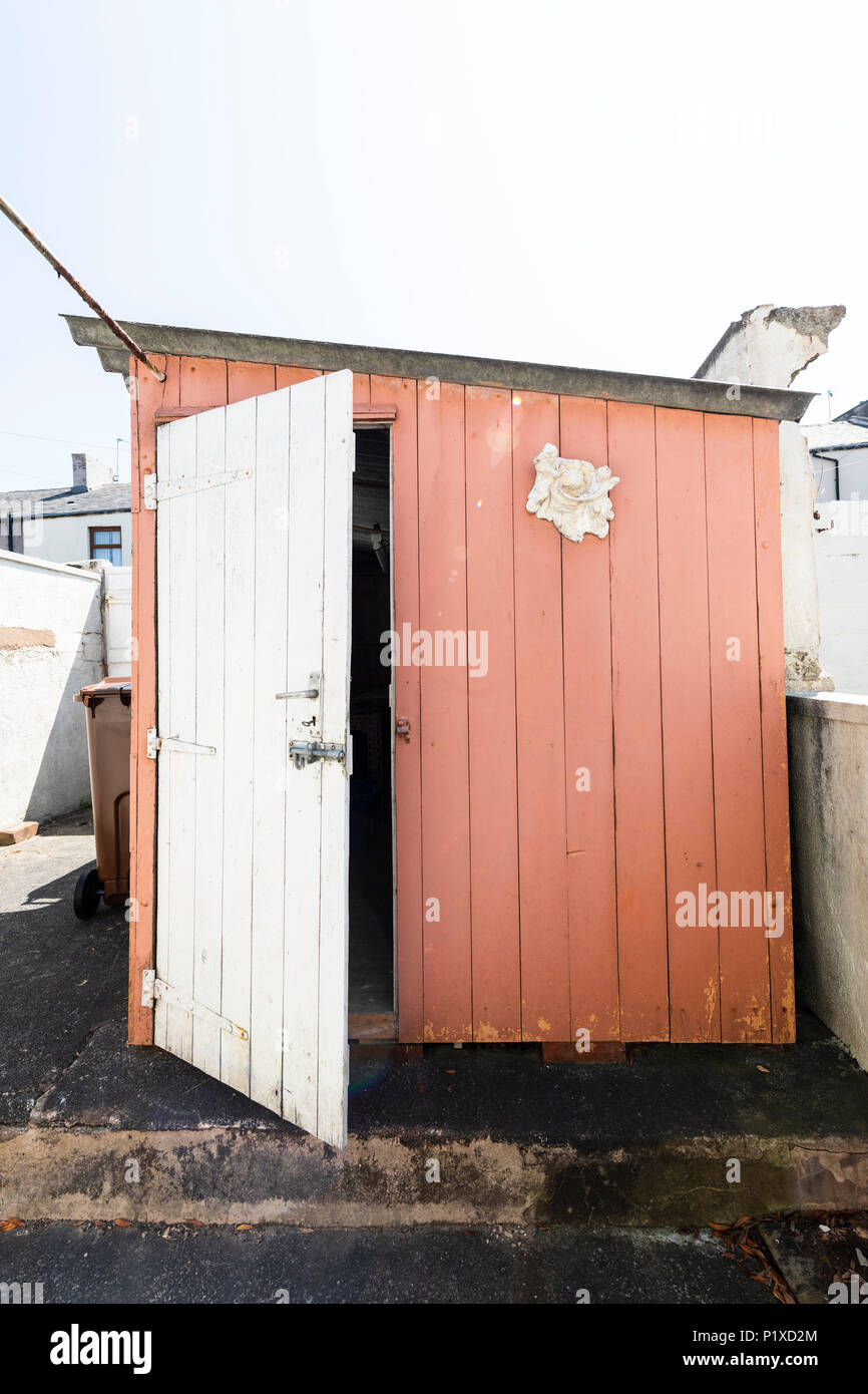Exterior of an old abandoned pink shed with white door in a northern England back yard. - Stock Image