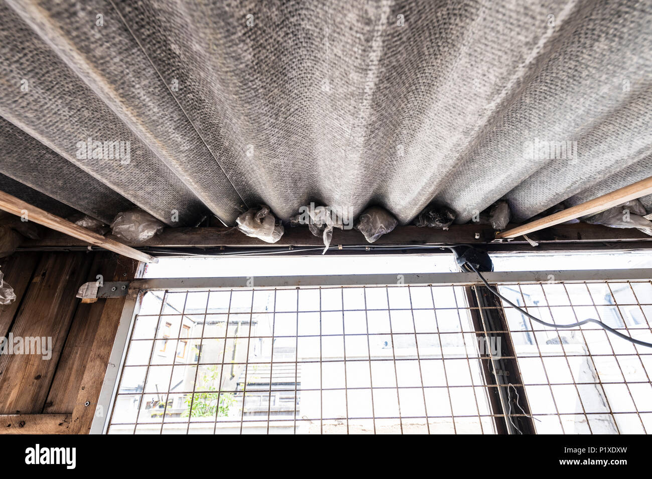 Old corrugated asbestos roof in an old shed - Stock Image
