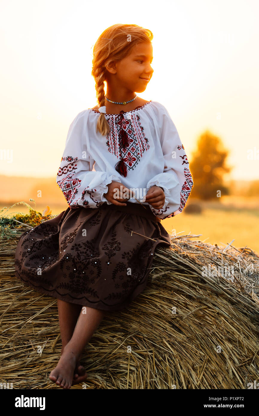 A girl in embroidered clothes in the field in the background of the setting  sun Concept of countryside lifestyle, national traditions