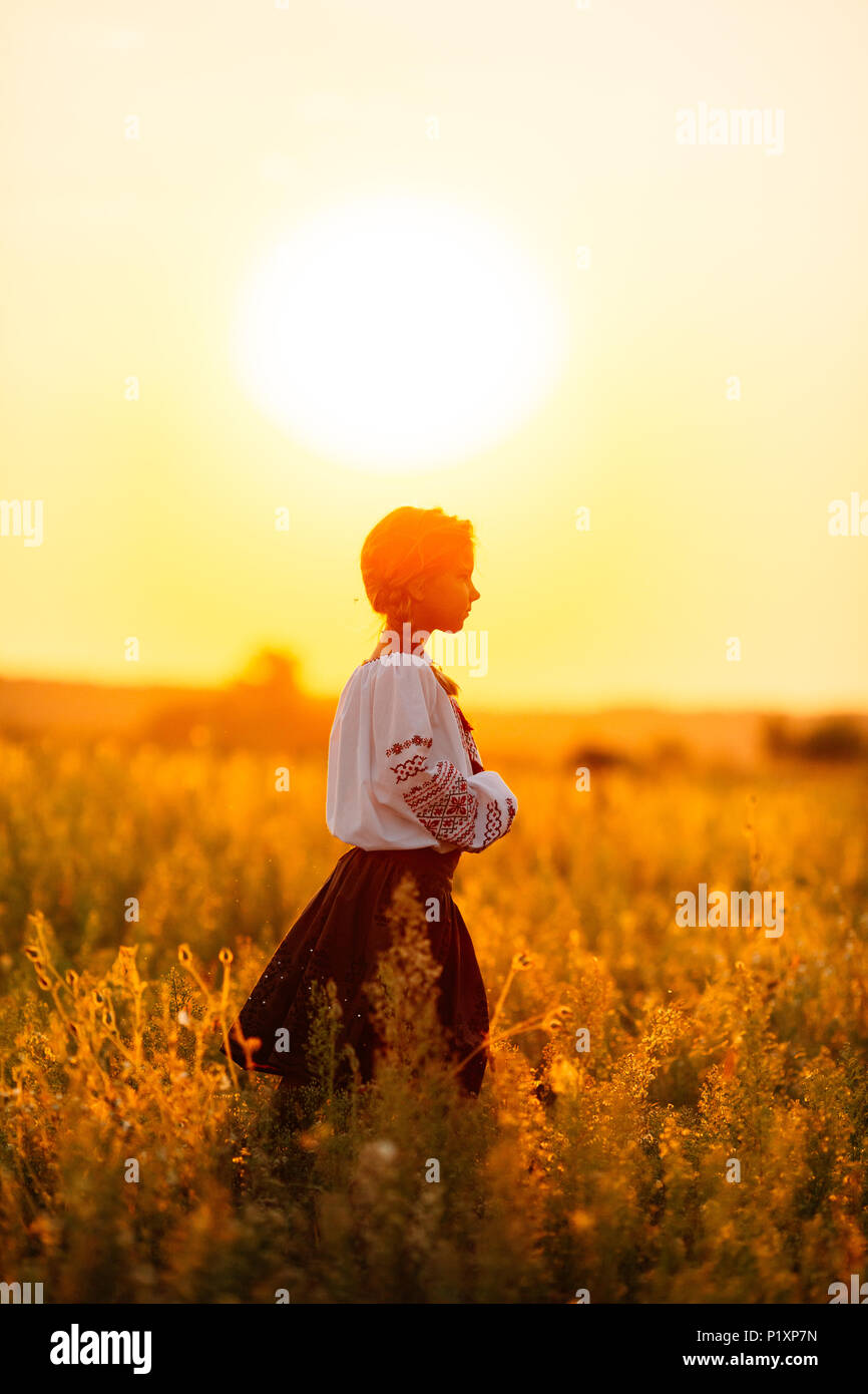 A girl in embroidered clothes walking along the field in the background of  the setting sun Concept of countryside lifestyle, national traditions