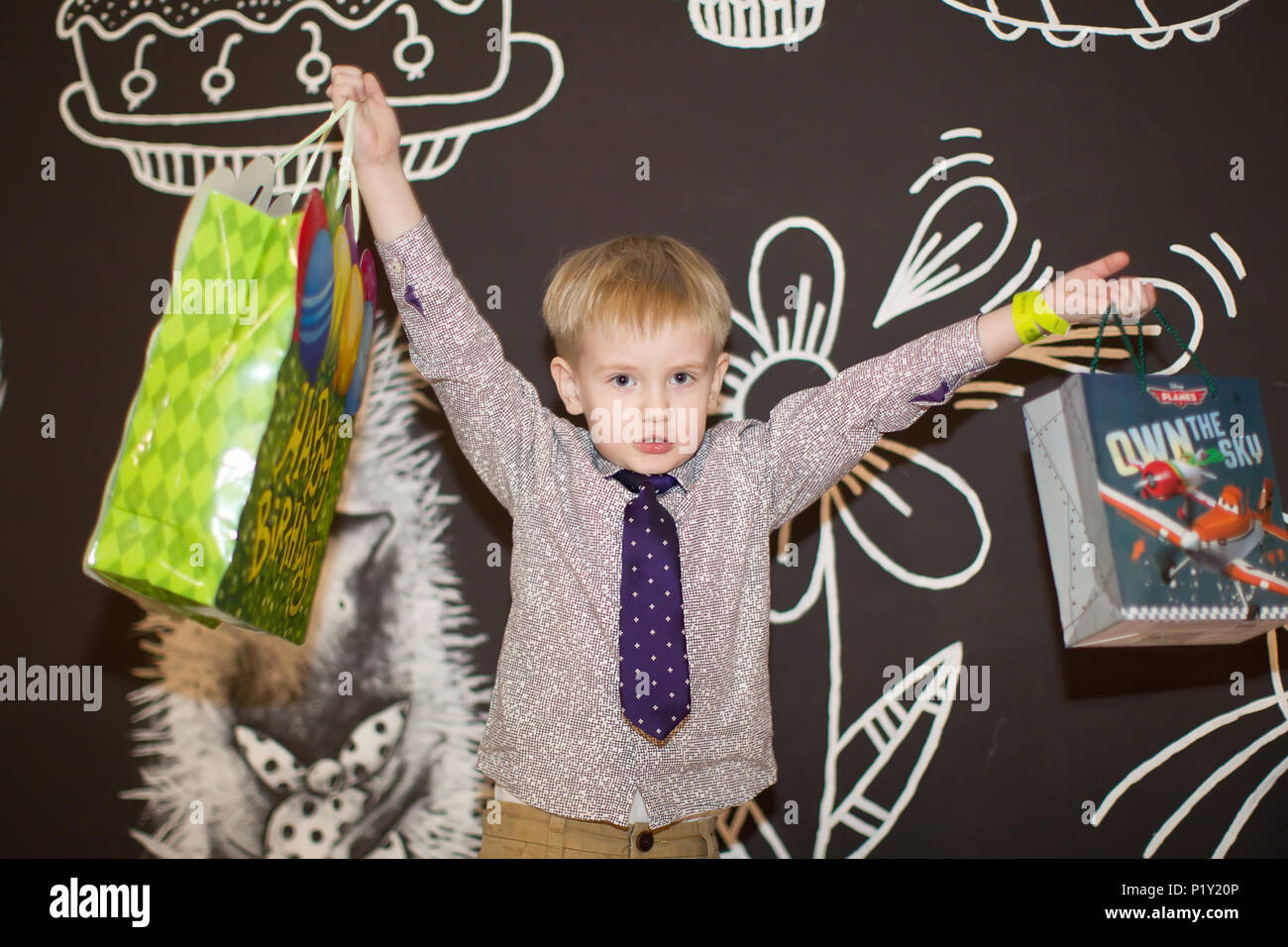 Belarus, Gomel, February 6, 2018. Children's entertainment center in the hypermarket. Children's holiday.Joyful little boy with gifts - Stock Image