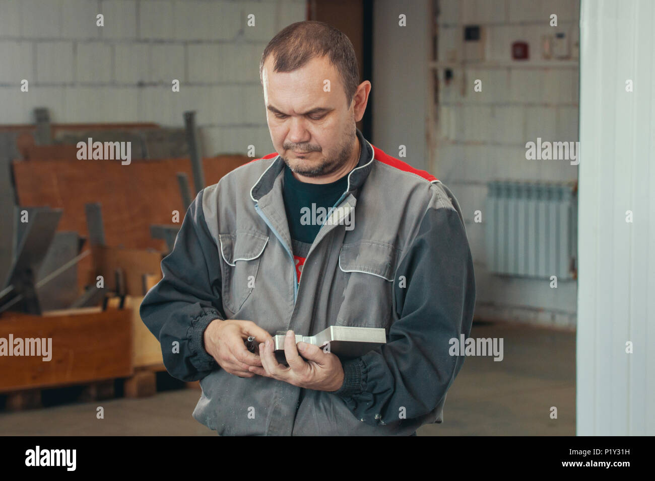 Adult man in uniform working with metal detail at CNC machine at factory with lathes Stock Photo