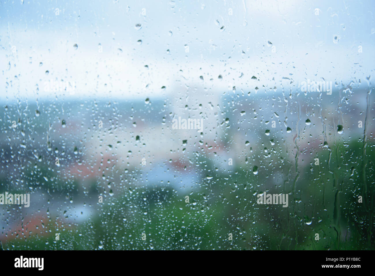 Rainy days - raindrops on the window, the city park blurred in the background - Stock Image