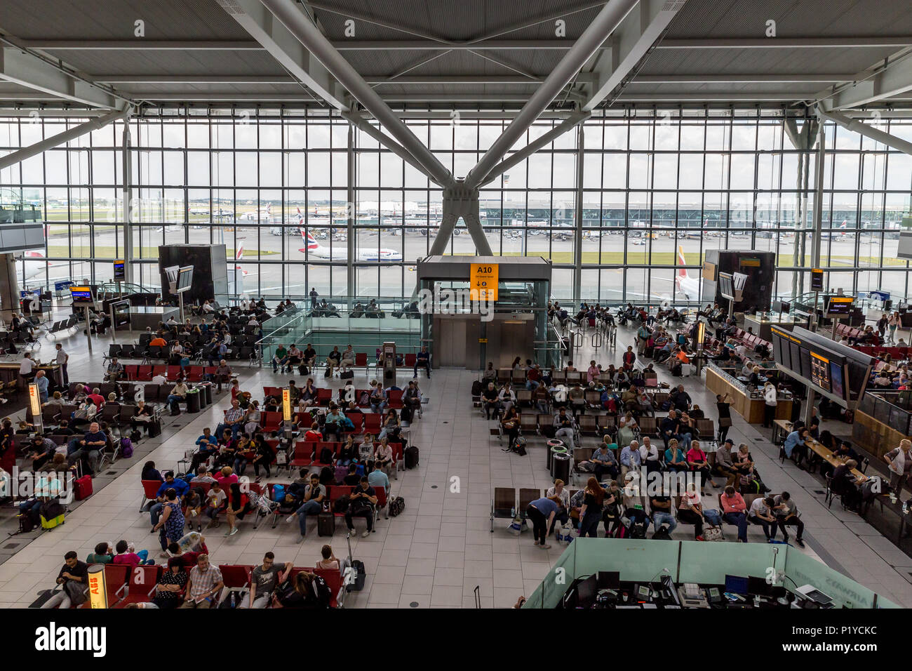 LONDON - MAY 27, 2018: Crowds of people waiting in departures to board plane at London Heathrow airport - Stock Image
