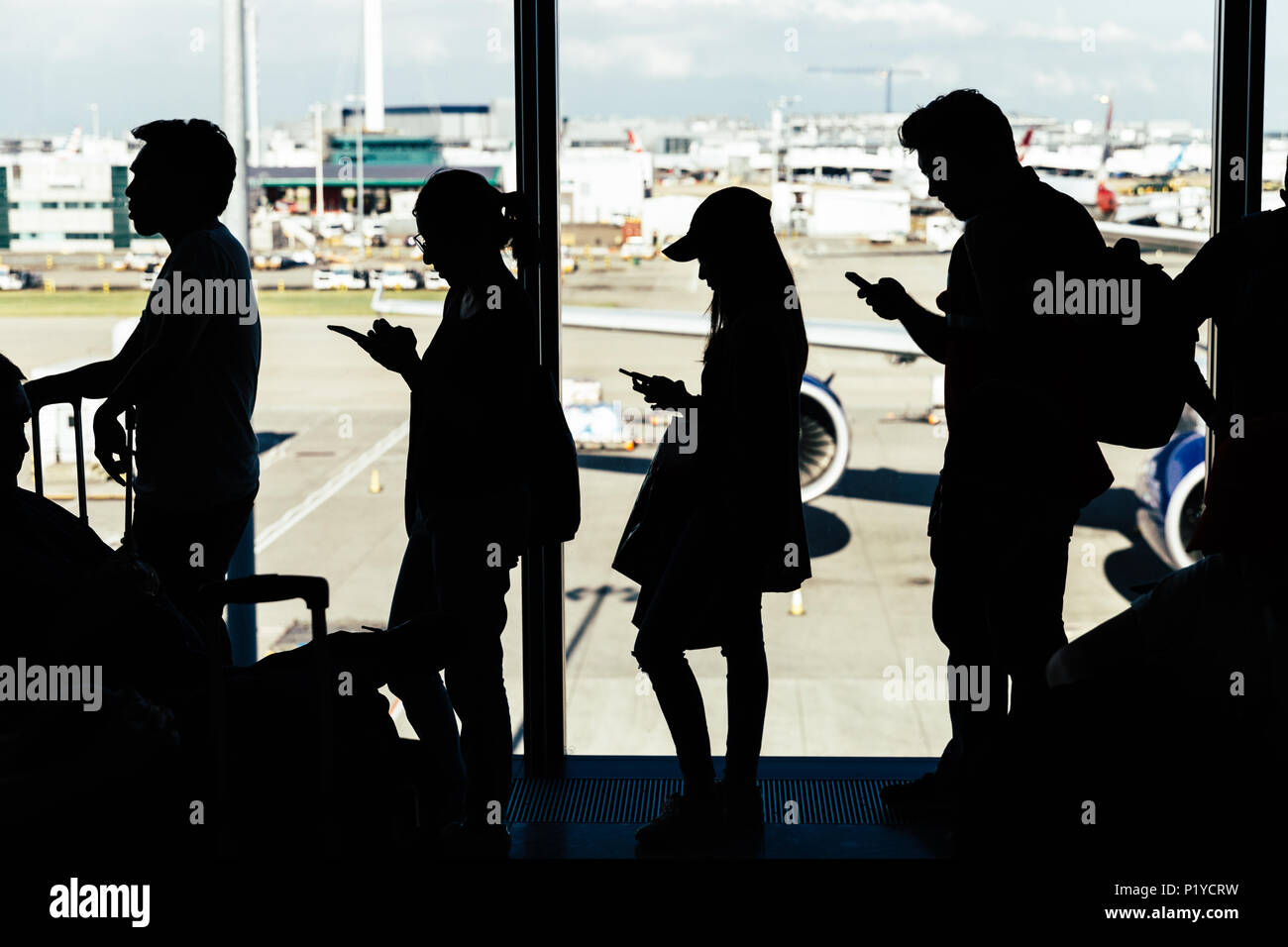 LONDON - MAY 27, 2018: People by windows waiting to board plane at London Heathrow airport - Stock Image