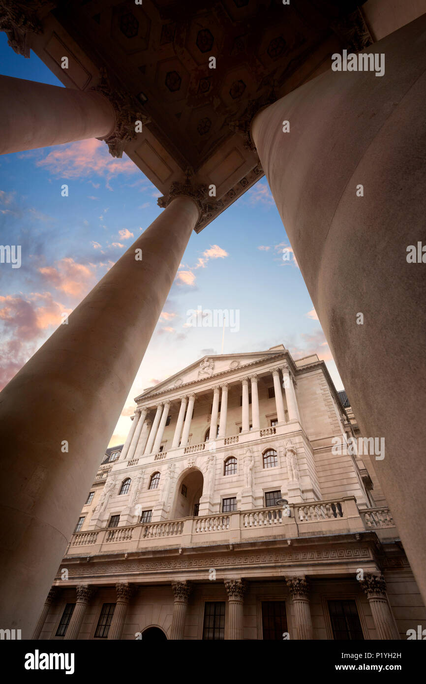 The Bank of England Heaquarters on Threadneedle Street in the City of London, England, viewed through the columns of the Royal Exchange at Sunset - Stock Image