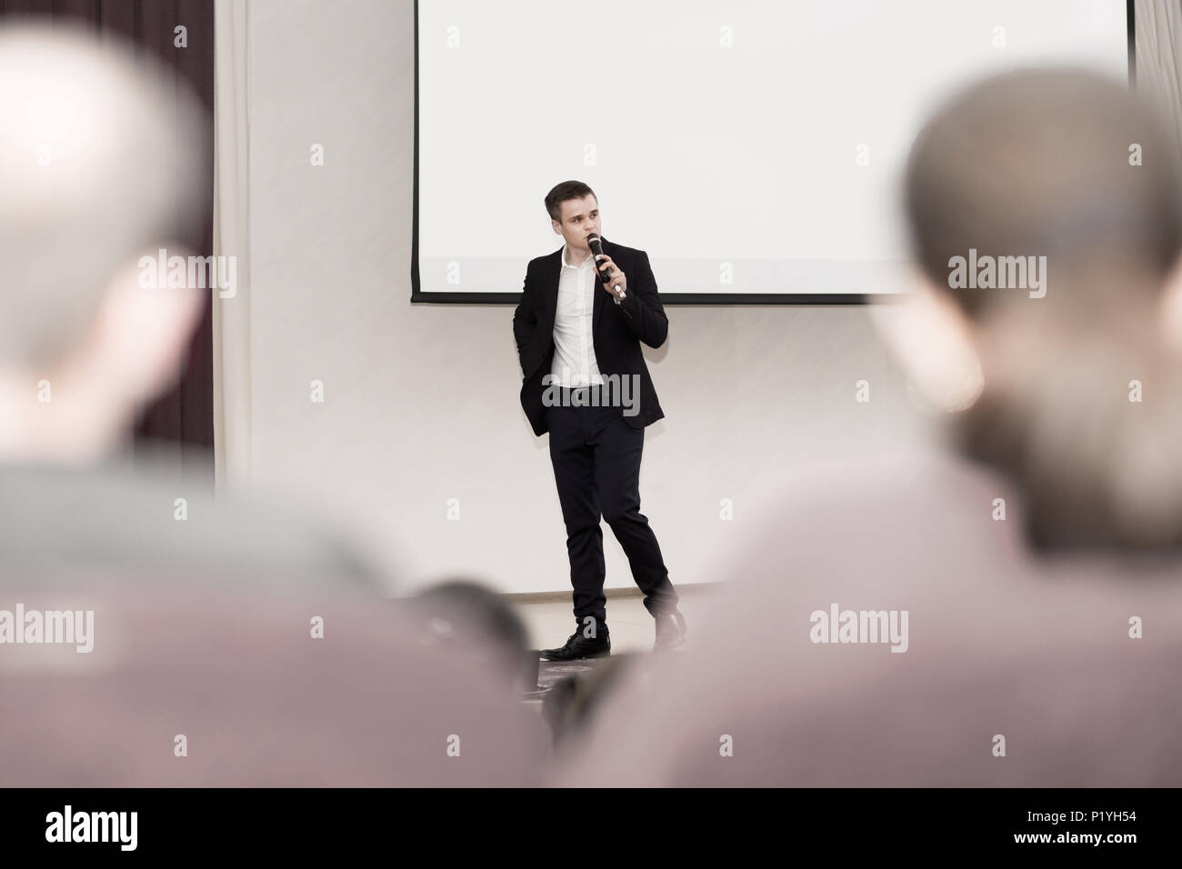 speaker conducts the business of the conference standing in front of a large white screen on the stage in the conference room - Stock Image