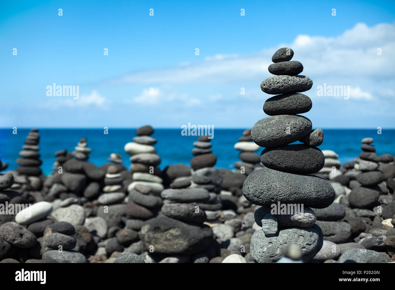 Stones pyramids on pebble beach in Tenerife, Canary Islands, Spain. Concept of harmony and balance - Stock Image