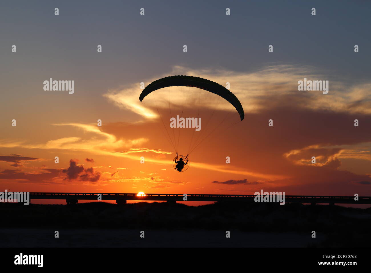 The silhouette of a powered paraglider, paramotor, in front of an orange sky in southern Texas, USA. The sun at dusk with a thundercloud cumulonimbus. - Stock Image
