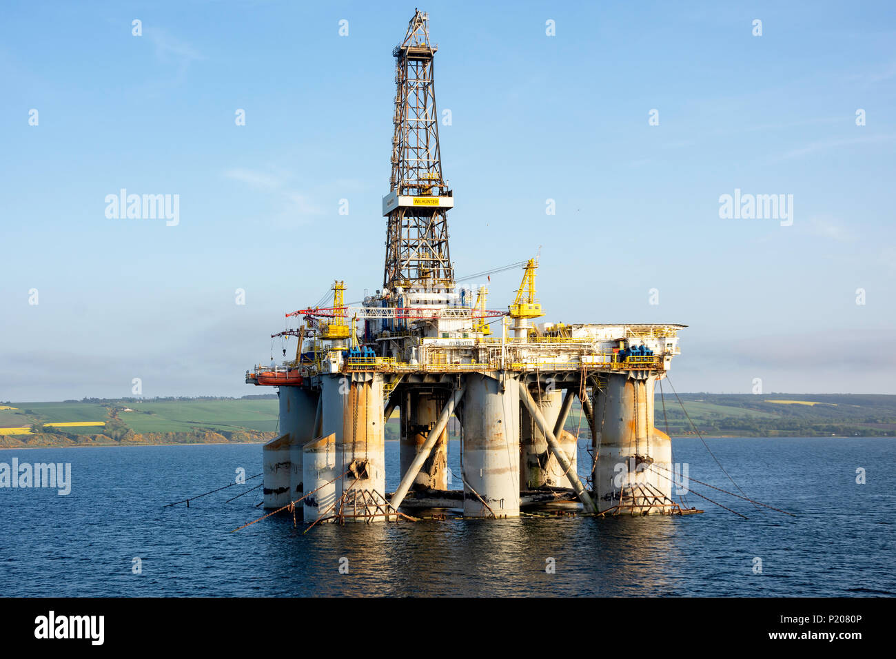 Oil rig anchored in the Cromarty Firth at sunset, Invergordon, Highland, Scotland, United Kingdom - Stock Image