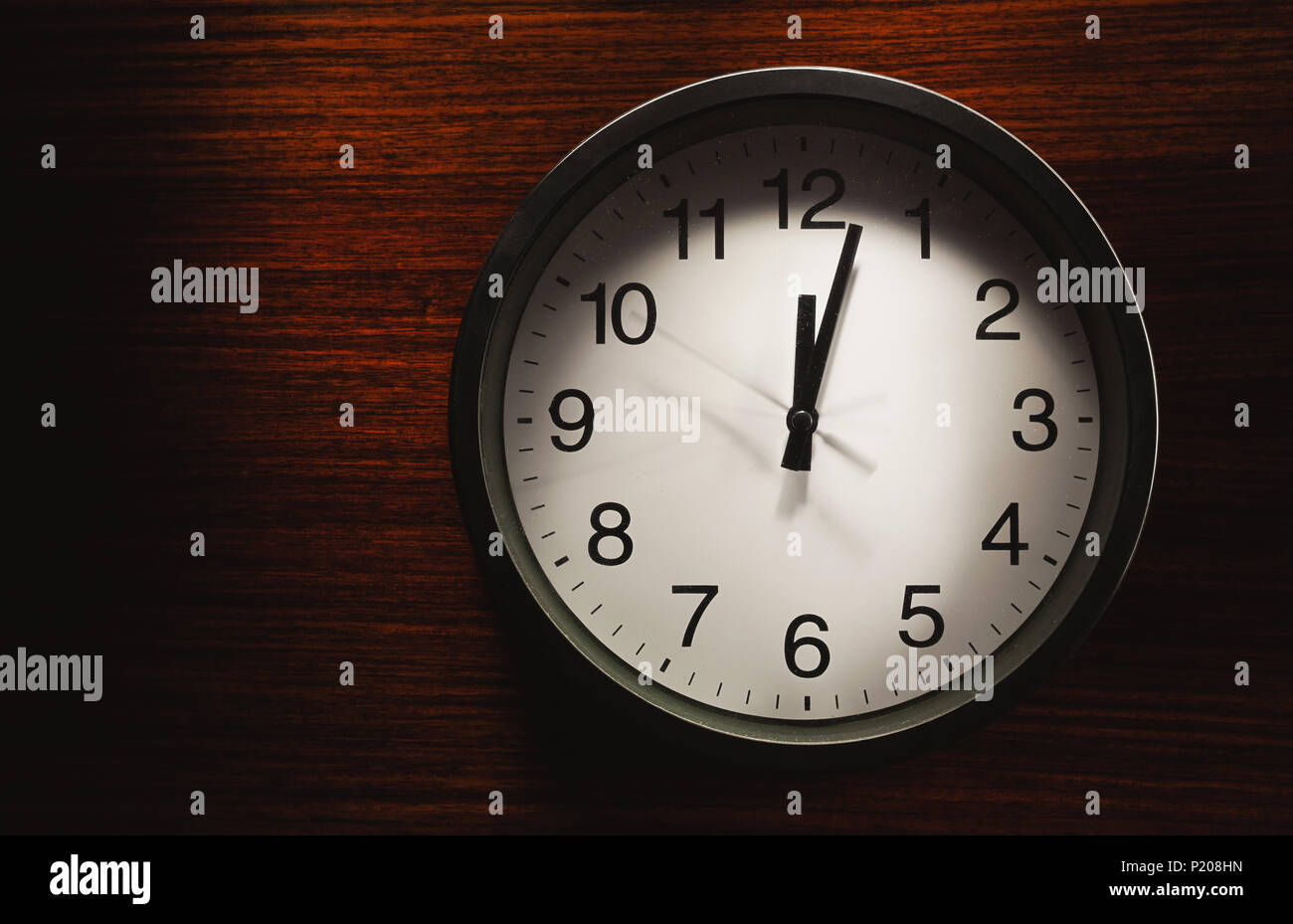 Simple composition, black wall clock on wooden surface showing twelve o'clock. - Stock Image