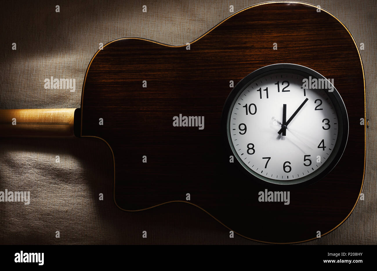 Simple composition, black wall clock on bed blanket showing twelve o'clock and part of an old retro gypsy style, acoustic guitar. - Stock Image