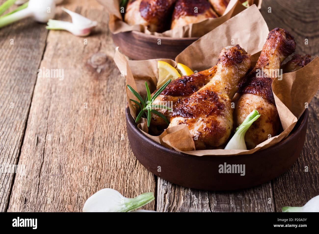 Roasted chicken drumsticks in ceramic bowl on rustic wooden table, favorite meal - Stock Image