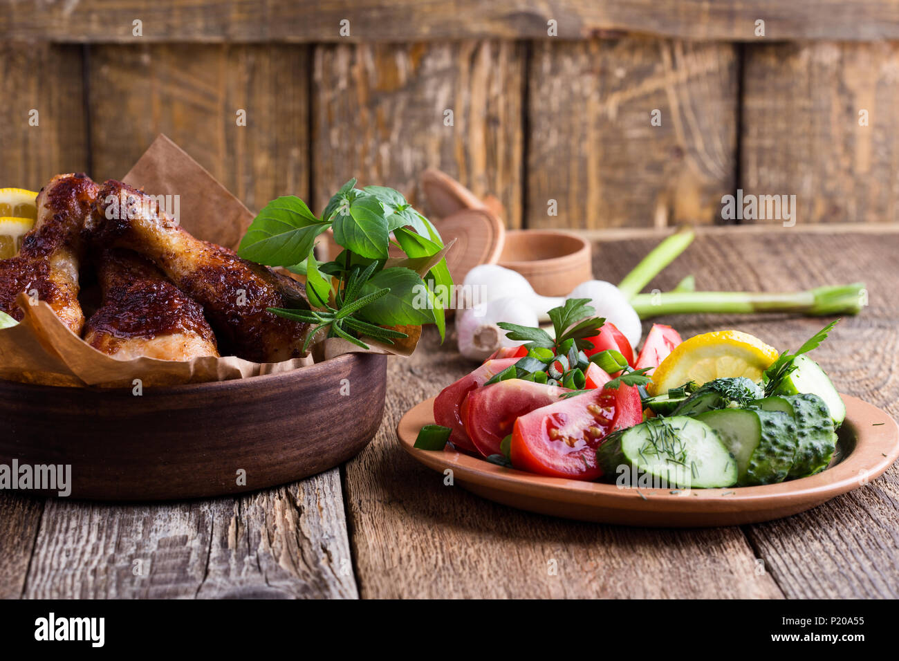 Roasted chicken drumsticks in ceramic bowl and fresh vegetables on rustic wooden table, favorite meal - Stock Image