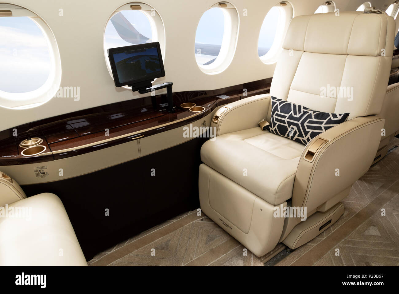 Comfortible cabin chair in a modern business jet during flight. - Stock Image