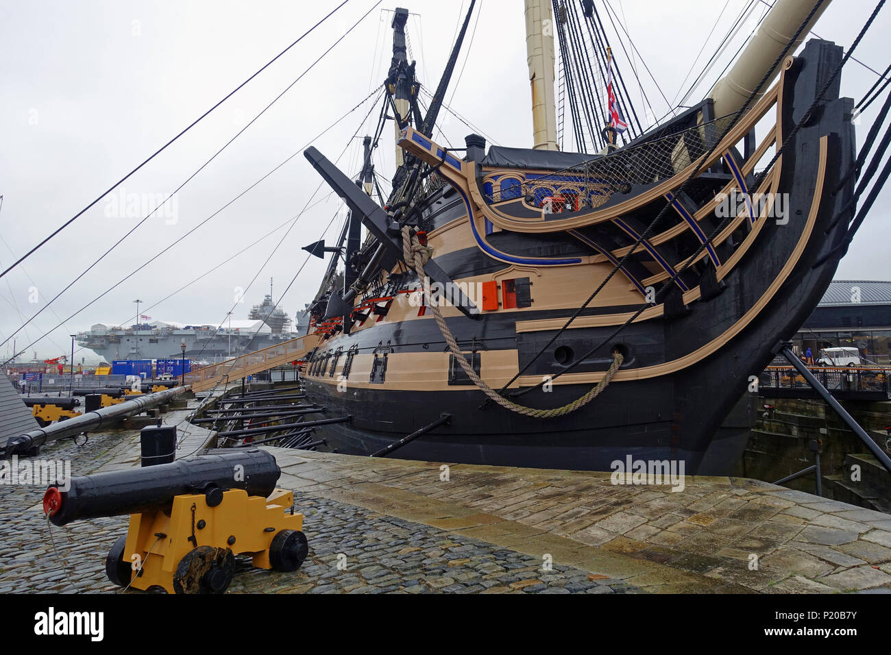 Britain's oldest commissioned warship, HMS Victory, and her newest and largest-ever, HMS Queen Elizabeth, on a rainy day in Portsmouth Harbou - Stock Image