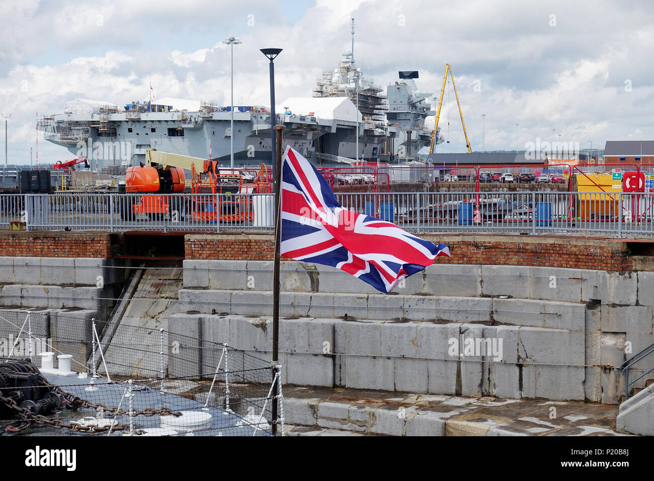 Union Jack on the Jackstaff of museum ship HMS M33 with newmaircraft carrier HMS Queen Elizabeth undergoing modifications at Portsmouth Dockyard - Stock Image