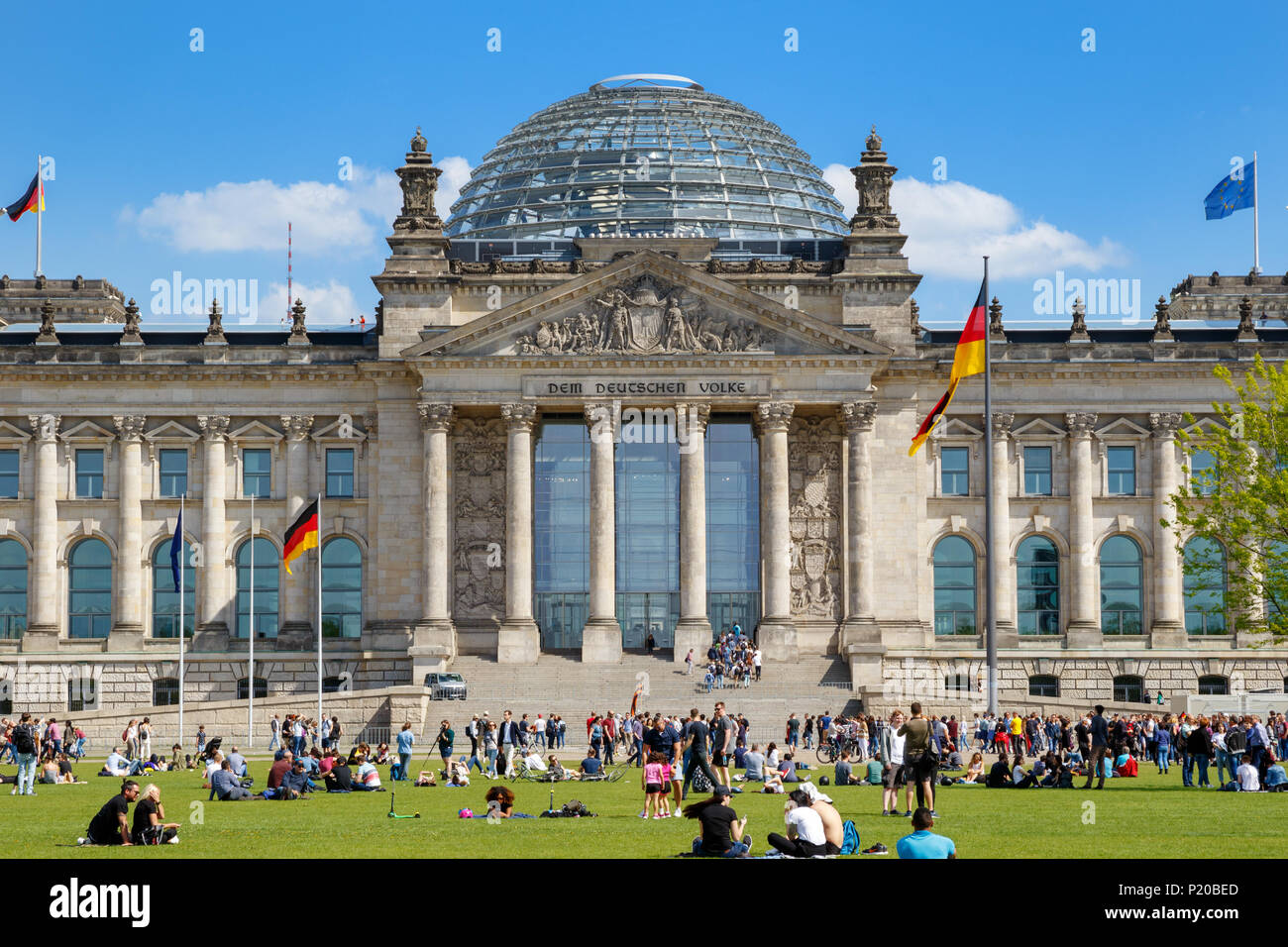 BERLIN, GERMANY - APR 28, 2018: People relaxing on the grass in front of the Reichstag building, seat of the German Parliament (Deutscher Bundestag). - Stock Image