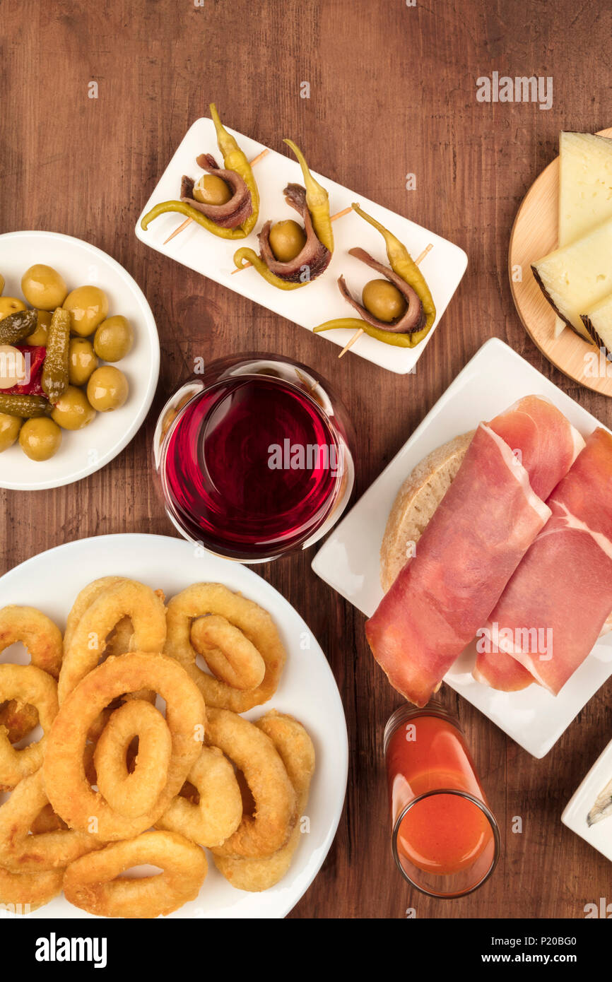 The food of Spain. An overhead photo of different Spanish tapas, shot from above on a dark rustic texture. Jamon, wine, calamari rings, gildas, gazpac - Stock Image