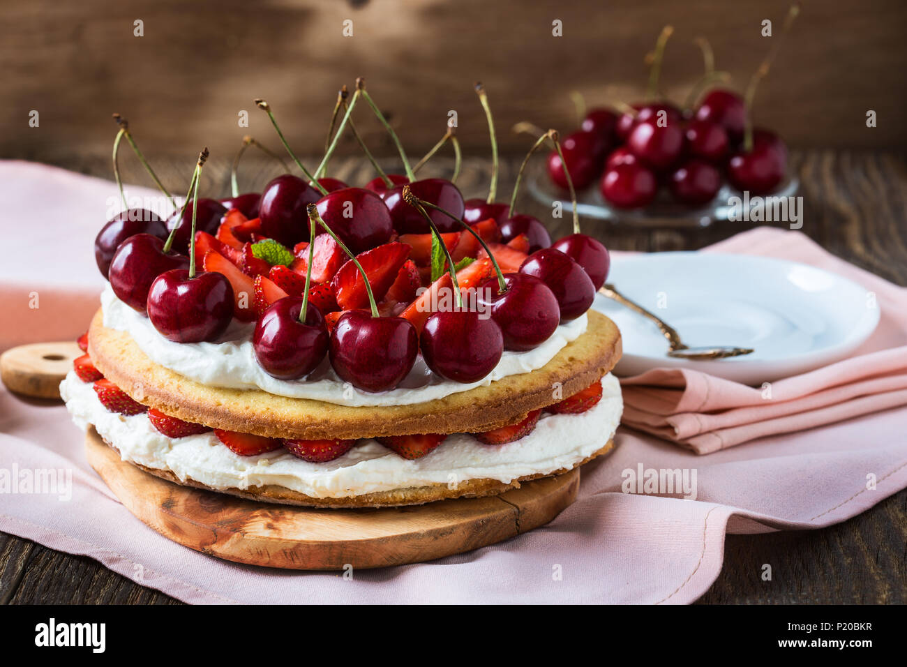 Homemade cream layer cake, fresh, colorful, and delicious dessert with juicy strawberries, sweet cherry, and whipped cream - Stock Image