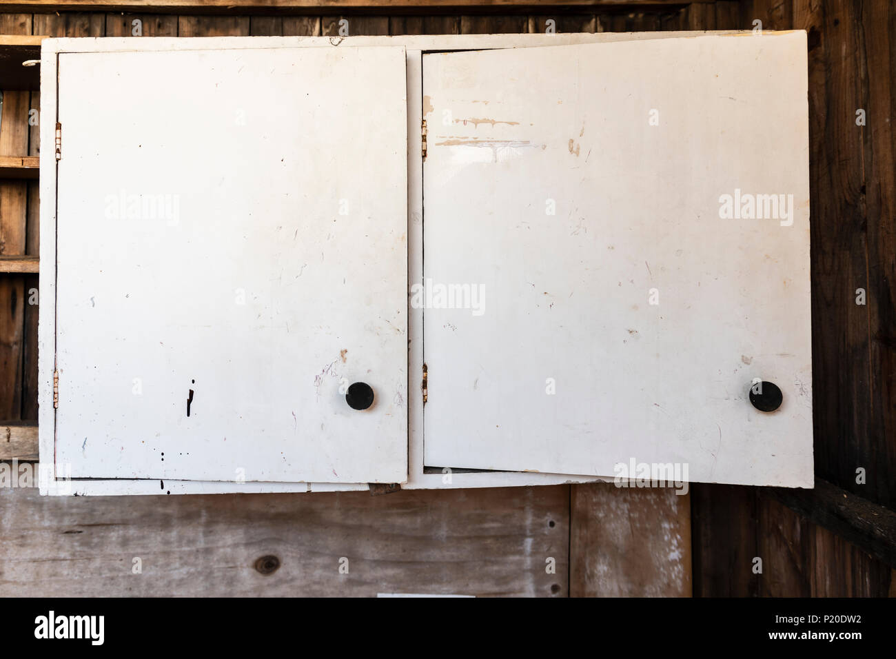 Old dilapidated cupboard in a shed - Stock Image