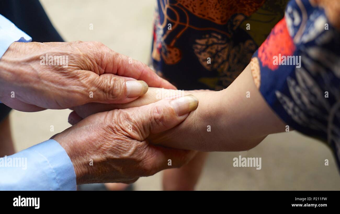 (180613) -- NANCHANG, June 13, 2018 (Xinhua) -- Liao Binsheng massages the foot of his daughter at home in Yushui District of Xinyu City, east China's Jiangxi Province, June 12, 2018. Liao Binsheng, 68, has taken care of his disabled daughter Liao Yonghong for 40 plus years. With a wife in bad health condition and a daughter born with cerebral palsy, Liao carries the whole burden of the family. With the help of local government, Liao found a job at a local library, and also earns money by planting vegetables and recycling wastes besides his work. (Xinhua/Hu Chenhuan) (zwx) - Stock Image