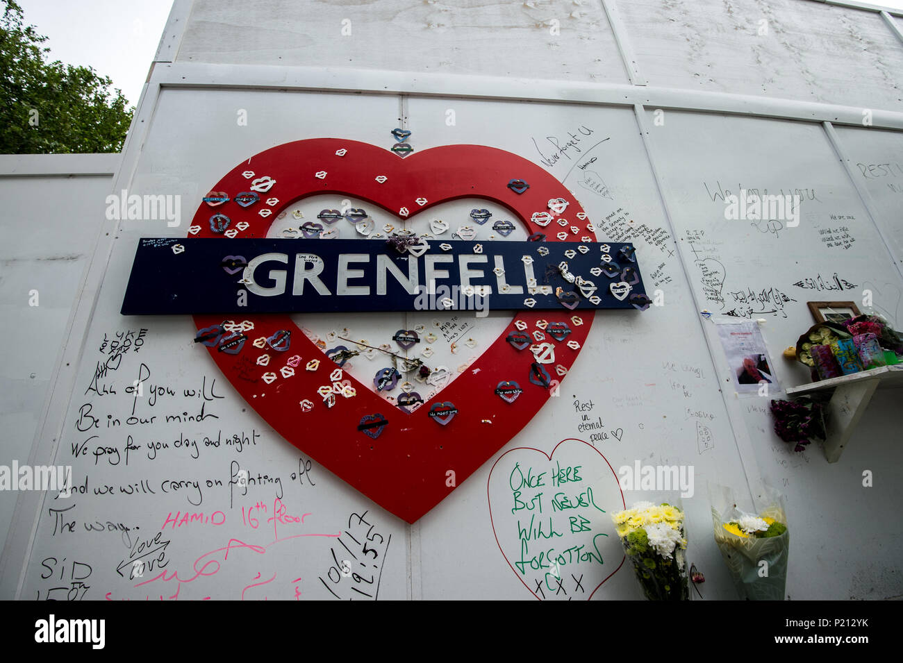 London, UK. 13th Jun, 2018. Grenfell's logo with massages at the foot of the tower. On the first anniversary of the Grenfell Tower fire, the area around the tower has been filled with flowers, candles and messages to remember those who lost their lives. Credit: SOPA Images Limited/Alamy Live News - Stock Image