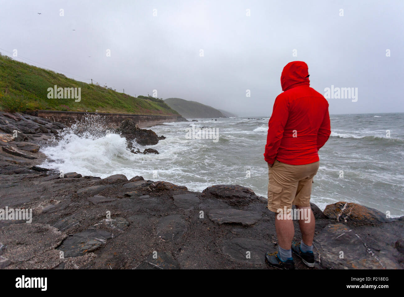 Rame Peninsula, Cornwall, England, 14th June 2018. UK Weather – The Met Office named storm, Storm Hector crashes into the UK unusual for this time of the year with winds up to 70mph. Storm Hector crashes into Cornwall with high winds and tides along the Cornish Coast at the harbour at Portwrinkle as a storm watcher watches waves crashing over the harbour wall, Cornwall © DGDImages/AlamyNews - Stock Image