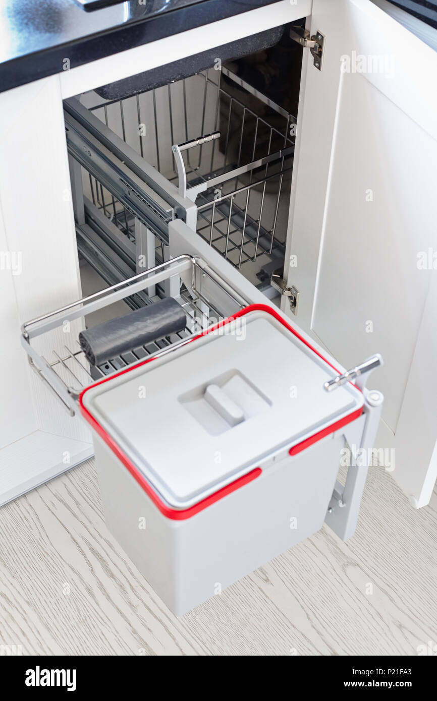 A solution for storing the trash can in the kitchen cupboard under the sink. Corner unit with a pull-out shelf for the trash can. - Stock Image