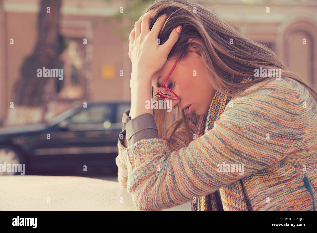 Side profile stressed sad young woman sitting outdoors with broken down car on background. City urban life style stress - Stock Image