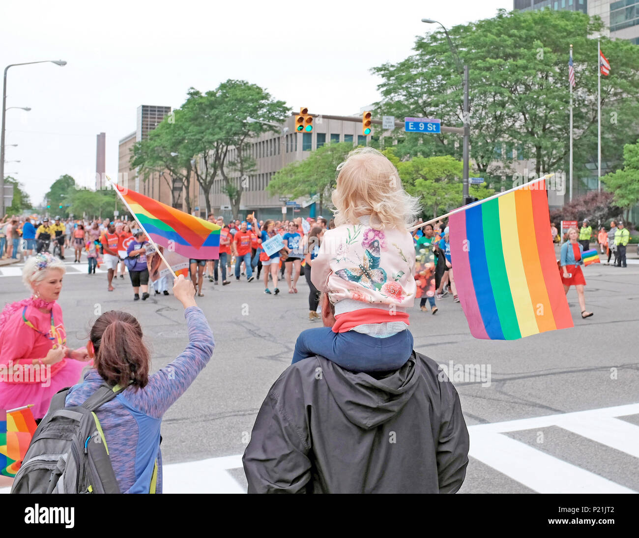 Young girl on dad's shoulders waves a rainbow flag, alongside her mom, as the 2018 Pride parade makes its way through downtown Cleveland, Ohio, USA. - Stock Image